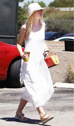 Elle Fanning wears a white maxi dress with a lace hem, top handle bag, flat sandals, and a felt fedora