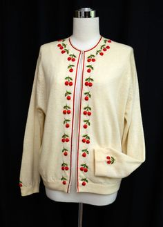 A fabulously cute and cozy 1950s cream cardigan with darling red and green cherries.