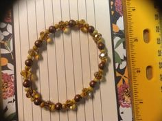 A beaded bracelet made with brown and amber colored beads strung on stretch cord.