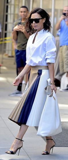 Victoria Beckham perfects business chic in a stylish blouse and pleated skirt as…
