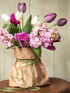Brown-Bag Special     Arrange flowers in a sturdy, wide-mouth vase or jar, positioning the heavier flowers, such as the lilacs, around the rim and adding tulips, with stems left long, in the center. Slip the vase into a large lunch-size brown bag, and roll down the top a couple times to make a cuff. Tape or staple the bag in the back to make the cuff fit snugly around the vase. Tie with twine.