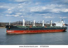 Empty bulk carrier cargo ship with deck cranes sailing on a river calm water by Olivier Le Queinec, via Shutterstock