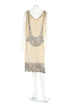 A beaded ivory and pink tulle flapper dress, circa 1925. A beaded ivory and pink tulle flapper dress, circa 1925. un-labelled, the ground entirely covered with opalescent sequins, the hem and bodice with floral motifs in pink and green sequins against a black beaded background, bust 96cm, 38in. - See more at: http://kerrytaylorauctions.com/one-item/?id=76&sub=%20&auctionid=429#.dpufe
