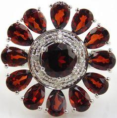 Garnet & Diamond Ring 10kt White Gold.  A flower shaped garnet and diamond white gold ladies ring in a size 6.75