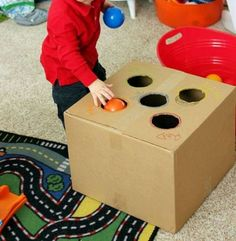 Cut out holes in a carboard box and provide items such as balls for posting