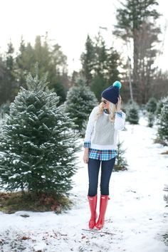 Red rubber boots, grey sweater, blue plaid blouse, dark and light blue pompom beanie hat