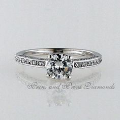 Centre diamond is 0.90ct H/VS1 Round brilliant cut diamond with 0.40ct GH/VS round diamonds set in shank of an 18k white gold band