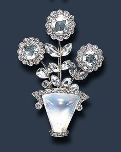A DIAMOND AND MOONSTONE BROOCH The cabochon moonstone vase, accented by single-cut diamond trim, extending three flowerheads, each centering upon a rose-cut diamond pistil, with circular-cut diamond petals and marquise and pear-shaped diamond leaves, mounted in platinum and gold