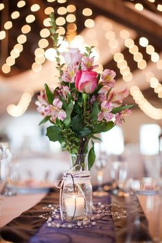 floral arrangement with roses and lilies and Mason jar with votive candle