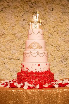 Towering wedding cake with very subtle Princess Belle inspiration. Love the red rose details creeping up the bottom