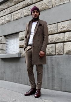 SMART CASUAL: tweed overcoat; brown trousers; leather belt and shoes; white jumper; beanie