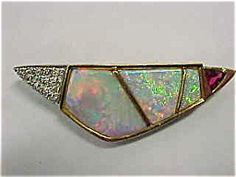 This unusual custom made 18kt yellow gold diamond-ruby-opal pin has a three dimensional design. The opals have beautiful color, fire and quality. The opals are surrounded by (28) round brilliant full cut diamonds