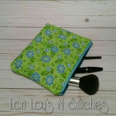 Green and turquoise floral zipper pouch approximately 7x9 inches.