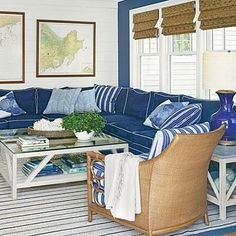 Navy sofas with white piping, blue throw pillows, and and a striped rug complete the nautical look of this comfy Massachusetts living room.