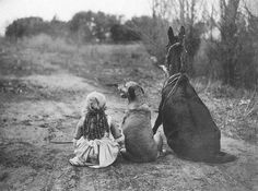 Little girl, dog and horse sitting on the road