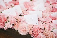 escort cards on a bed of carnations.  #wedding #decor