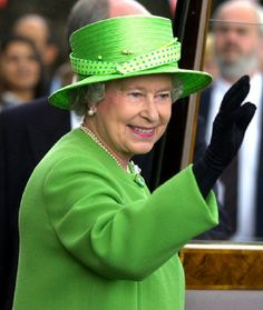 Queen Elizabeth II in bright green outfit and hat waving to the crowd as she arrives at the Brewhouse Arts Centre in Burton, while visiting the area on her Golden Jubilee tour in 2002