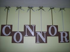 paintable, textured wallpaper squares  painted brown  painted letters hanging on ribbon thumbtacked to the wall
