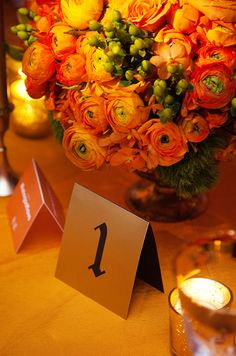 Illuminated by a nearby votive candle, a black and gold table number sits under a ranunculus centerpiece.