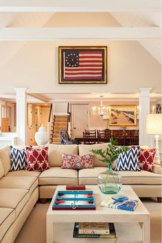 "This coastal cottage mixes neutral walls with classic nautical colors. The wall color in the living room is ""Benjamin Moore Manchester Tan"". Love the framed antique flag."