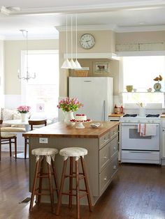 Cottage Kitchen with white appliances; Island in the middle difference color with butcher block counter top.
