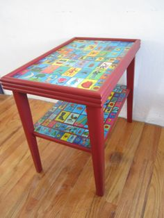 A completely one of a kind two tiered solid wood table painted red and covered with vintage inspired Mexican Loteria cards and a satin polyurethane to protect the cards and table.