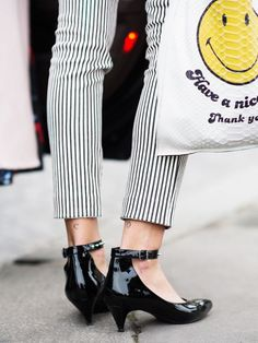Carlotta Oddi wears striped skinny pants, ankle-strap kitten heels, and a graphic leather tote bag