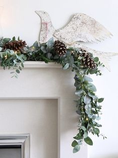 love this fresh christmas garland with eucalyptus pine cone and fairy lights on mantelpiece with vintage metal dove. Click through for more creative christmas flower arrangement DIY ideas to try in your own home this holiday period Christmas Lights Garland, Blue Christmas Decor, Metal Christmas Tree, Light Garland, Christmas Table Decorations, Christmas Diy, Christmas Wreaths, Christmas Pine Cones, Xmas