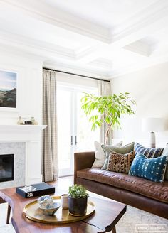Pillows, plant, tabletop styling, ceiling detail. Light but warm vibe. This is a good update for the ALL WHITE living rooms from a few years ago.