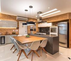 Que charme essa Cozinha Gourmet  Amo as paredes revestidas de tijolinhos e a mesa de jantar apoiada no balcão! Otimizou o espaço com originalidade e sofisticado!!  Por Moderne Arquitetura