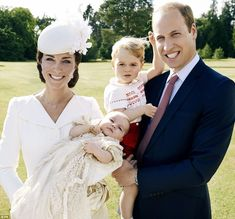 Prince George plays with his hair as the family of four pose for their first official snap...