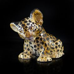 """Lot #238: Ceramic Leopard Figurine DESCRIPTION: Ceramic figurine hand crafted and painted depicts a baby leopard painted in hues of black and golden brown. The figurine shows the leopard slightly tilting his head, marked on the bottom """"Italy"""".  CIRCA: 20th Ct. ORIGIN: Italy DIMENSIONS: H: 8″ L: 10″"""