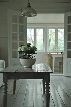 Everything about this is perfect. I love the table, the light fixture, the doors. The wide wood floors.   Beautiful.