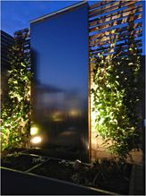 Water flowing vertically from a chosen height creates a mirrored effect in this garden which brings the night sky right down into the space creating a sense of volume. Up lighting with Spike Spots either side of the feature frames the space as well as creating dappled shadows on the trellis.