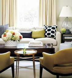 A classic modern living room with cream curtains, a white sofa with scattered graphic cushions and two yellow armchairs. The room has an unusual colour scheme of navy, cream and mustard yellow