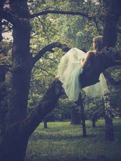 Girl daydreaming in a tree. Long white gown.