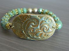 Stretch bracelet with a golden-green polymer charm connector and green glass beads