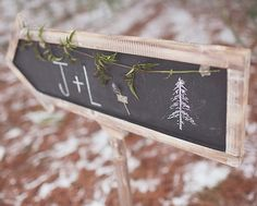 Chalkboard arrow sign pointing way to rustic woodland wedding.