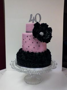 Glam 40th Birthday. Lots of ruffles on the bottom tier. You can't see detail because it's not a good pic. Gumpaste and fondant for decorations. Silver disco dust and silver and black edible pearls for bling. A gentleman wanted a pink, black and a little bling for his wife's 40th birthday and this is what I came up with. TFL!