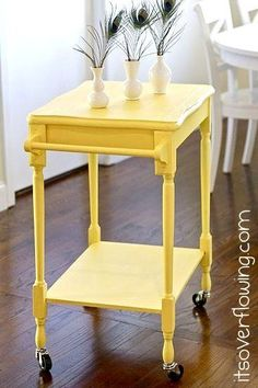 End Table into Kitchen Cart. Take one cute little table. Add towel bars to the sides. Add casters to the bottom of the legs. Paint.