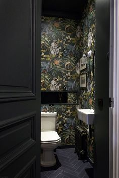 The stunning Savuti wallpaper by Cole & Son looks so striking in the dark charcoal colourway. This cloakroom is seriously stylish.
