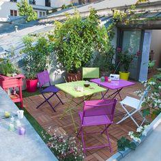 Terrasse sur les toits de la ville aménagée avec du mobilier Fermob coloré et un joli sol en parquet