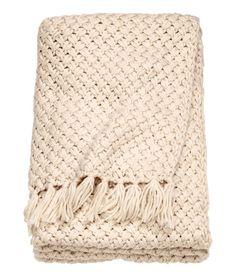 Light beige. Blanket in a soft knit with fringes on the short sides.
