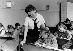 16 Feb 1943, Germany --- A girl of the German Girls League (BDM) teaches children at a school in the East, in February 1943. --- Image by © Berliner Verlag/Archiv/dpa/Corbis