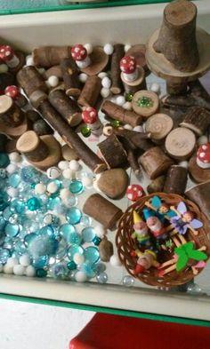fairy garden small world play w/ tree blocks, glass stones, pom poms, corks painted as toadstools, plastic flowers, fairies, gnomes, etc...