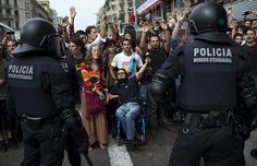 Barcelona, Spain: Riot police officers stand next to demonstrators protesting against high unemployment