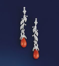 A pair of diamond and coral earpendants   Each composed of a pear-shaped coral, corallium, drop to a diamond floral panel articulated suspension and diamond cluster top