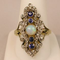A gorgeous Belle Époque opal, sapphire and rose-cut diamond ring.  Masterfully handcrafted in silver on 14-carat yellow gold. A soft and sweet round