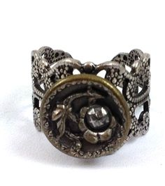 Antique Silver Metal Band Ring Flower Lace Band Ring Round Button Center One Size Fits All. Flower in Center of Ring. Stunning Unique Band Ring. Band is a little over 1/2 Inch at the largest part.