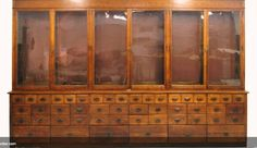 Would be wonderful as a wardrobe with hanging bars in top window cabinets! Old store display.